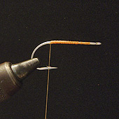STEP #1 Place a #1 mustad 34007 hook in your vice. Starting by the eye, cover the hook with some flat waxed Orange thread