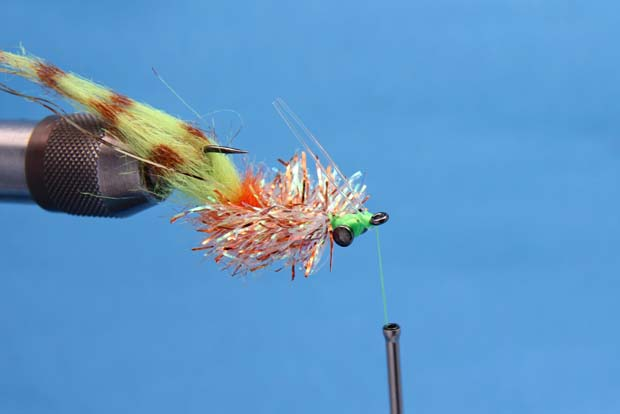 Step 10: Advance the thread forward to the eye of the hook, and tie in your favorite style of weed-guard (single or double post). Whip finish and cut away the thread. Trim the monofilament weed guard even with the barb of the hook.