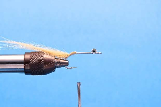 """Step 3: Measure a pair of EP Shrimp eyes so they extend past the bend of the hook about a 1/4"""" and tie them in on top of the hook shank to create an even body.  Separate the eyes around the bundle of Craft fur so they protrude away from the fly slightly on each side."""