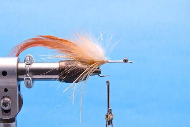 Step 6: Tie in a 6 inch piece of Bonefish Tan Cactus Chenille with several tight wraps. Make a few wraps onto of the palmered hackle so when you palmer the chenille the tie buts of the feather are hidden.