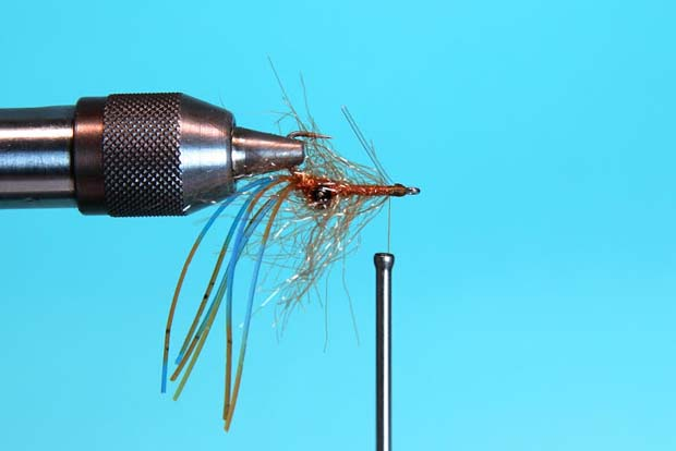 Step 6: Turn the fly over in the vise, and tie in a 30# mono post weed guard.  Trip the post off even with the barb  of the hook.  Whip finish behind the weed guard and cut away the thread. Apply a thin coat of Clear Cure Goo Hydro for a more durable fly.