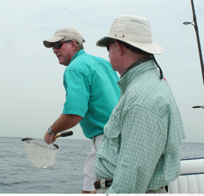 "Capt. Steve Anderson disperses live ""chummies,"" while Pat Ford waits to cast."