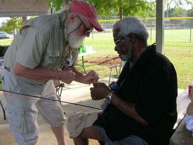 Project Healing Waters Fly Fishing lead Walter Shockley (left) helps Al Finley in learning to tie a fly on the tippet during at outing in Mount Pleasant. Photo by John Warland.