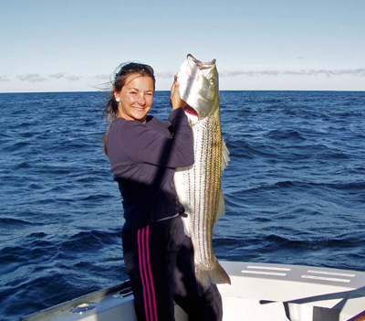 New Englander Angela Annino holds up an impressive striped bass. Image Credit: NOAA.