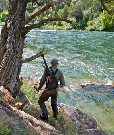 Fly fishing guide with Tenkara gear checks out high flow on mountain stream out West. Image credit Tenkara Guides LLC.