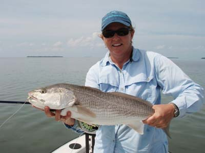 Website Angler Cindy Russell with nice red aboard Hunt's skiff. Image Capt. Dave Hunt.