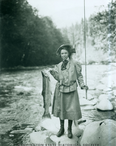 Pictured, Eleanor Chittenden, daughter of Brigadier General Hiram Chittenden, holds a steelhead trout on the Elwha River during an outing of the Mountaineers. Taken August 1, 1907, by Curtis Asahel. Photo provided courtesy of the Washington State Historical Society.