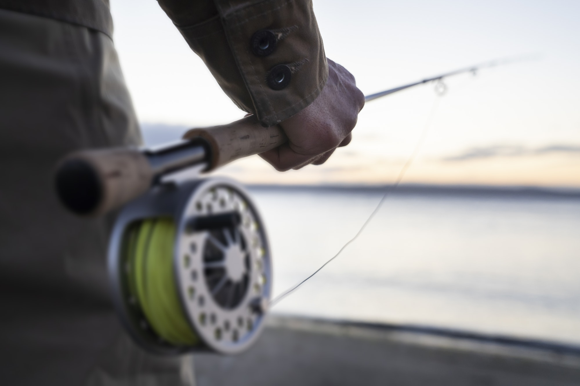 A closeup of a male hand holding a fly fishing rod and reel at the water's edge on a beach.