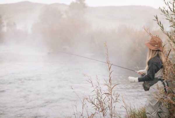 A fisherman, a woman standing on the banks of a river, flyfishing.