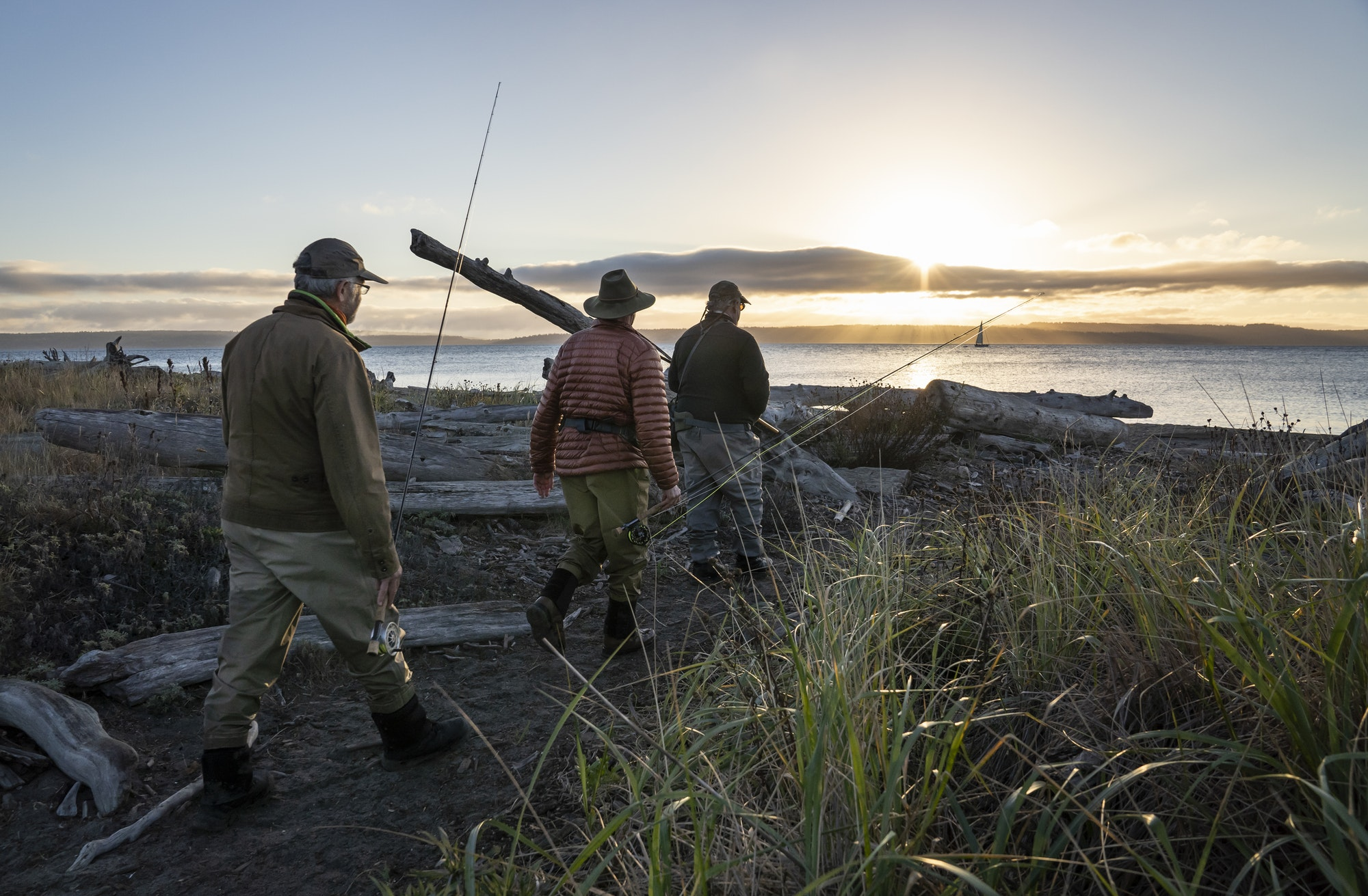 Two fly fisherman and a guide walk to a salt water beach at sunrise to fish for searun coastal