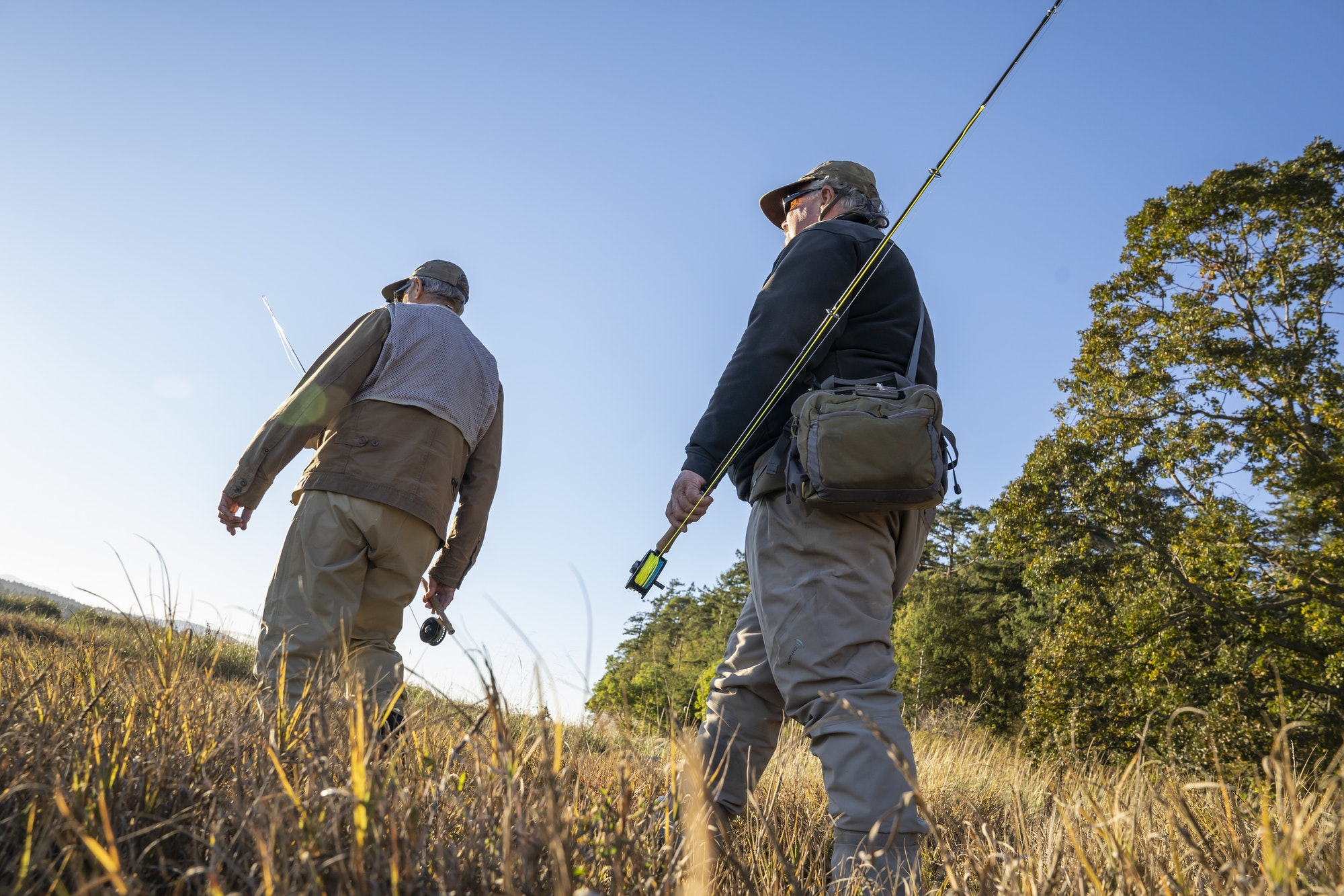 A view looking up at two fly fisherman walking a worn trail to a salt water beach in northwest