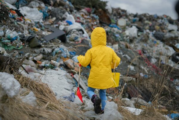 Rear view of small child walking on landfill, environmental pollution concept
