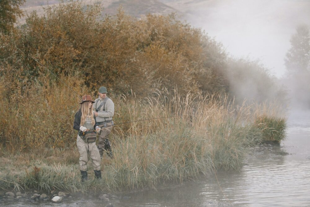 A man and woman standing on a riverbank, fishing.