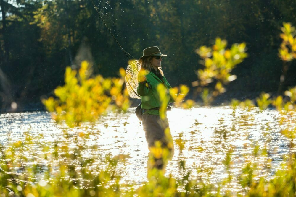 Fly fisherwoman casting & fishing on river, British Colombia, Canada.
