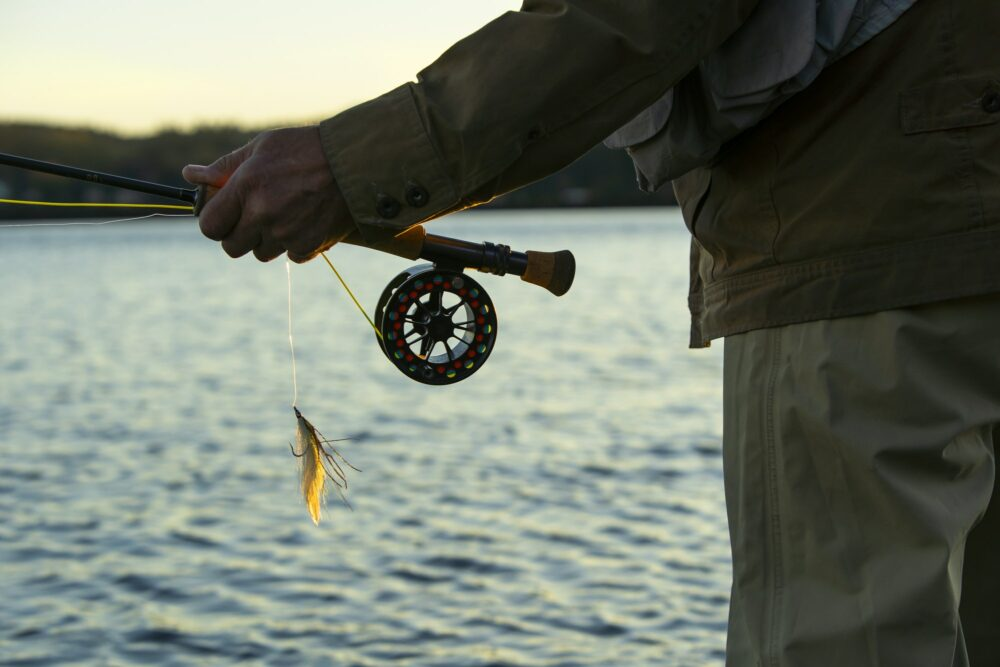 "A closeup view of the hands of a fly fisherman holding his fly rod and reel and a ""Lefty's Deceiver"""