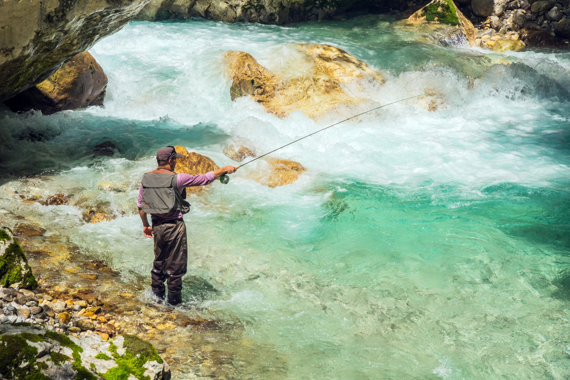 A fly fisherman fishing in a river