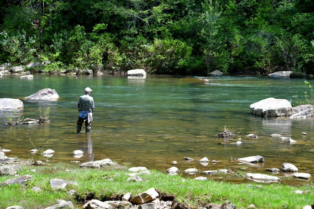 Fisherman fly fishing in a river in the mountains of Virginia.