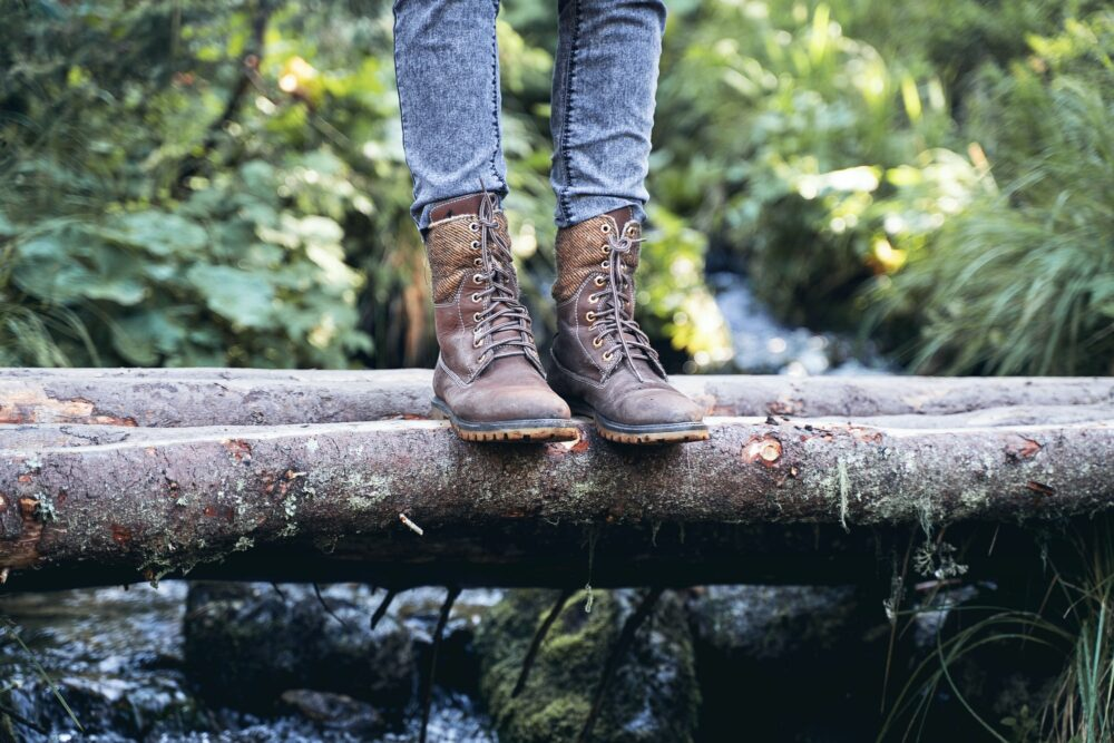 closeup of woman hiking boots on wooden bridge in the woods
