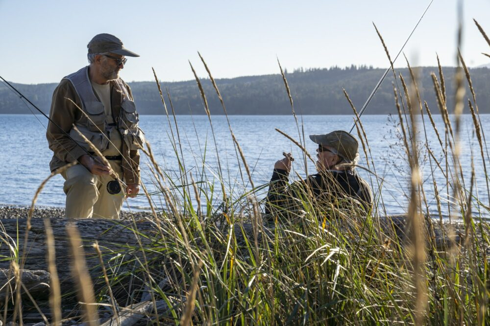 Two fly fisherman talk over techniques for fishing while standing on a salt water beach in northwest