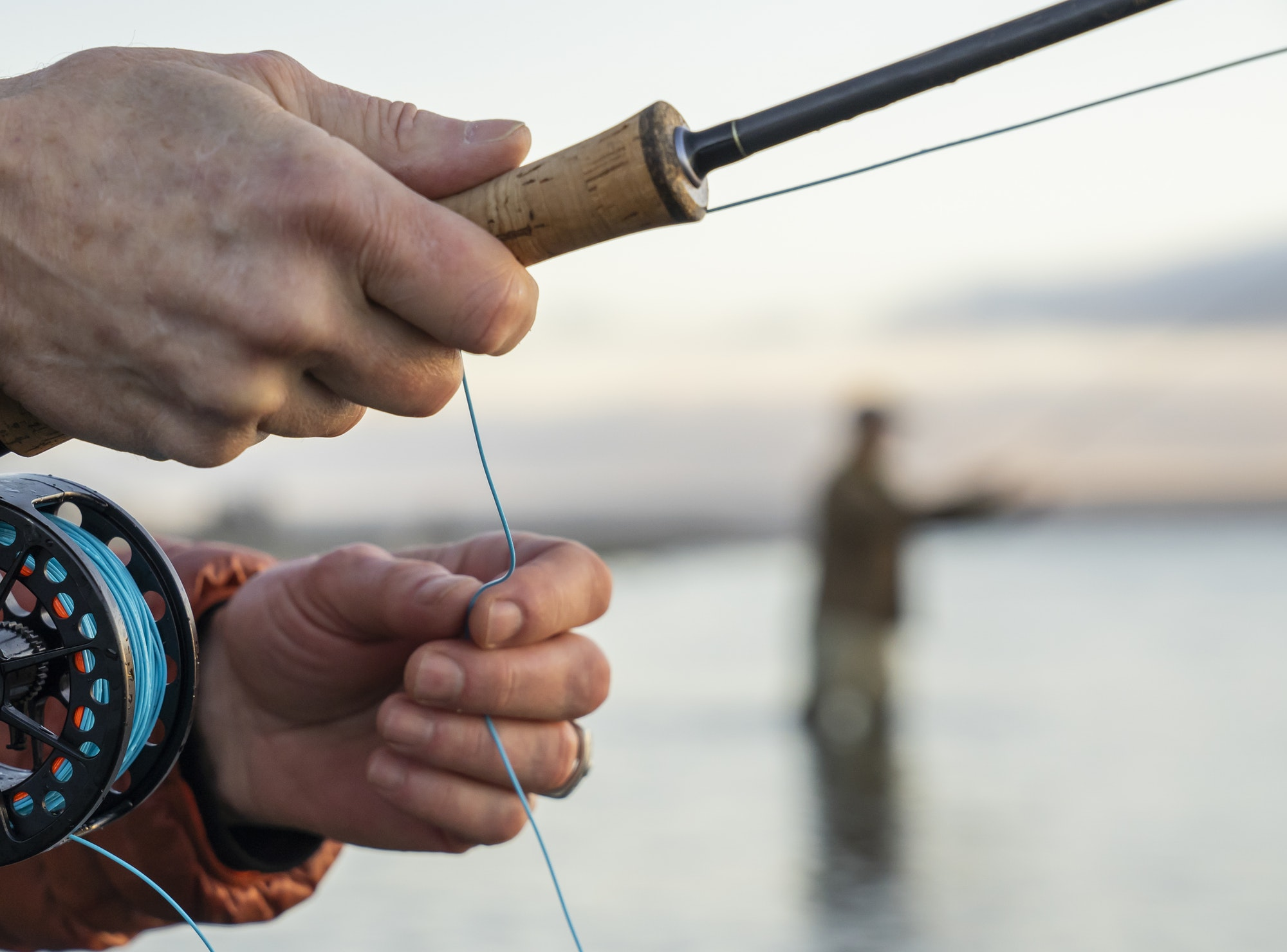 A closeup of a fly fisherman's hands holding his fly rod and line while fishing.