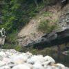 Man using rod fly fishing in rough river among mountain